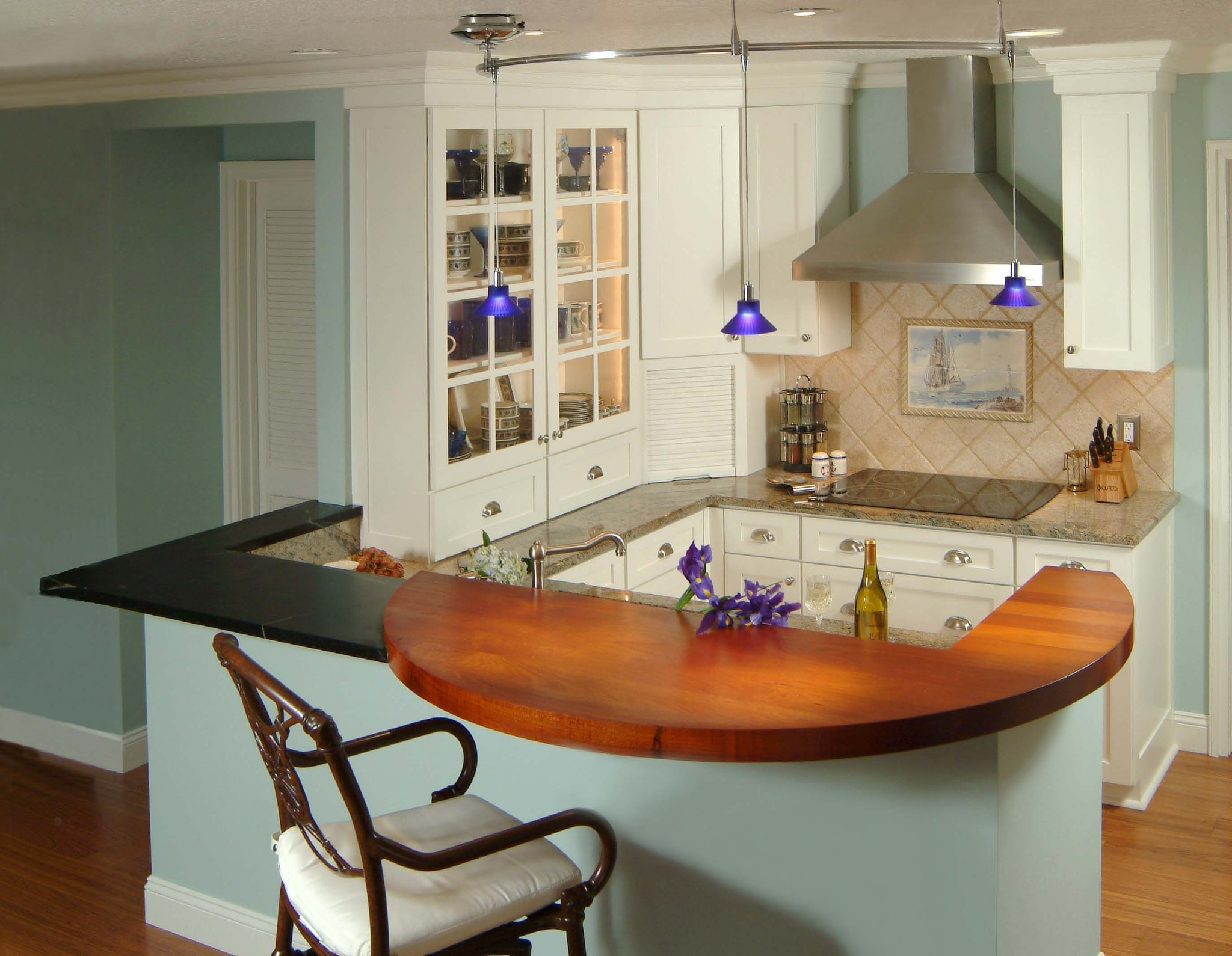 small contemporary kitchen with white cabinetry, peninsula seating at layered wood and stone countertops