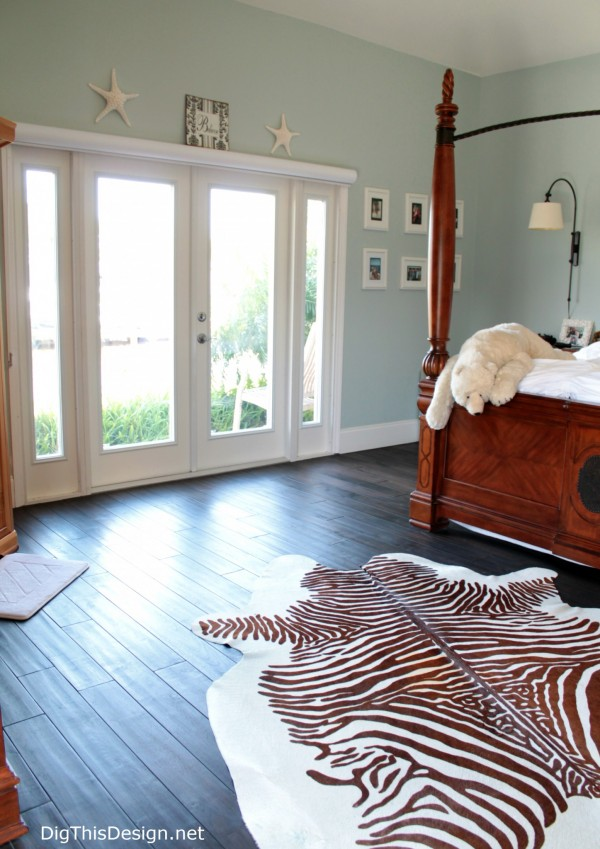 Transitional coastal master bedroom with French doors light blue green walls dark wood floors, wood canopy bed, zebra hide rug, room design by PDB Designs