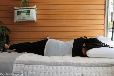 Person laying down on a memory foam mattress to test spine alignment and comfort.