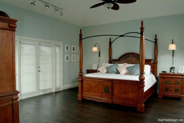 Transitional coastal style bedroom with dark walnut wood floors, wood post bed, light blue walls and minimal decor.