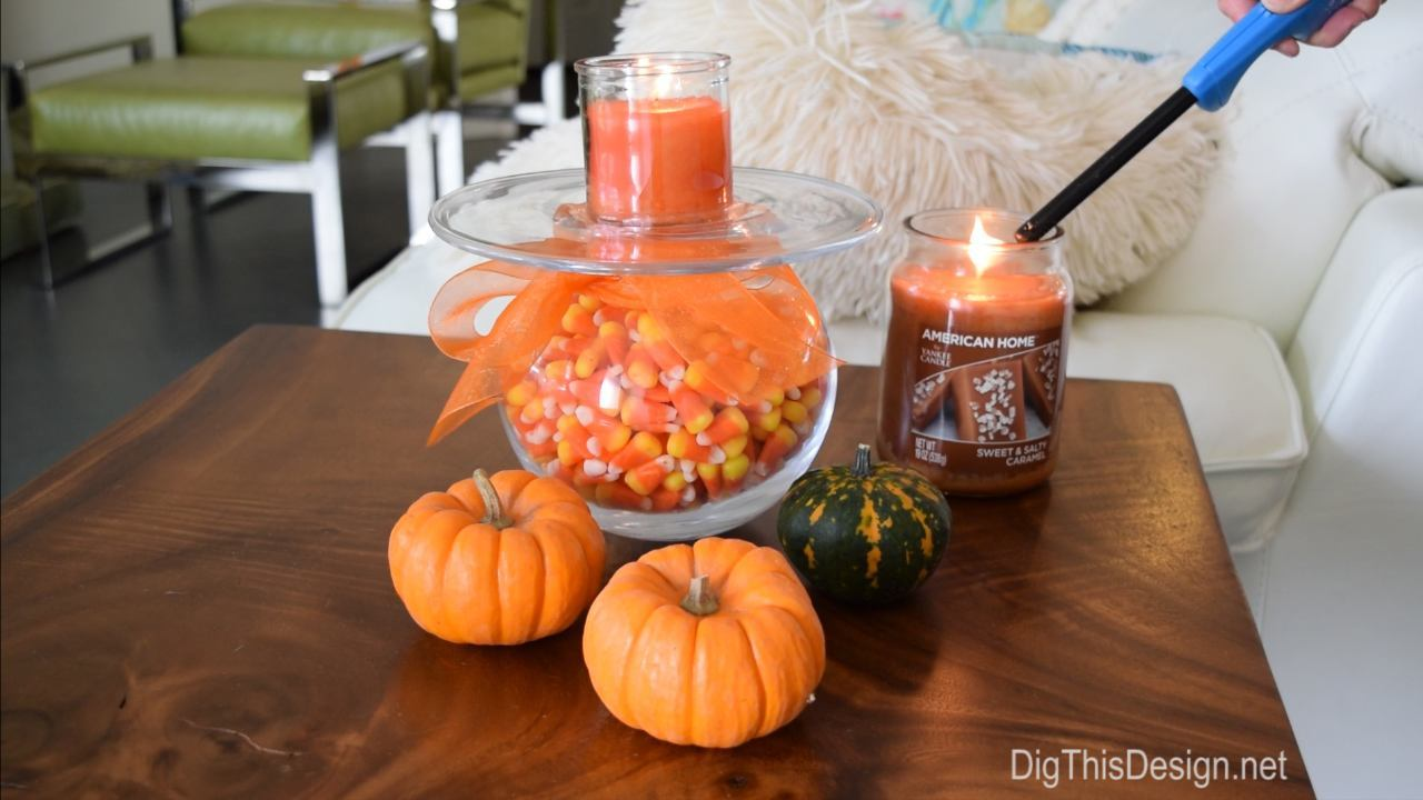 Living room wood slab table with DIY Halloween decor project. Glass vase wrapped in orange tulle ribbon holding candy corn next to tiny fresh pumpkins and squash with American Home by Yankee Candle fragrances