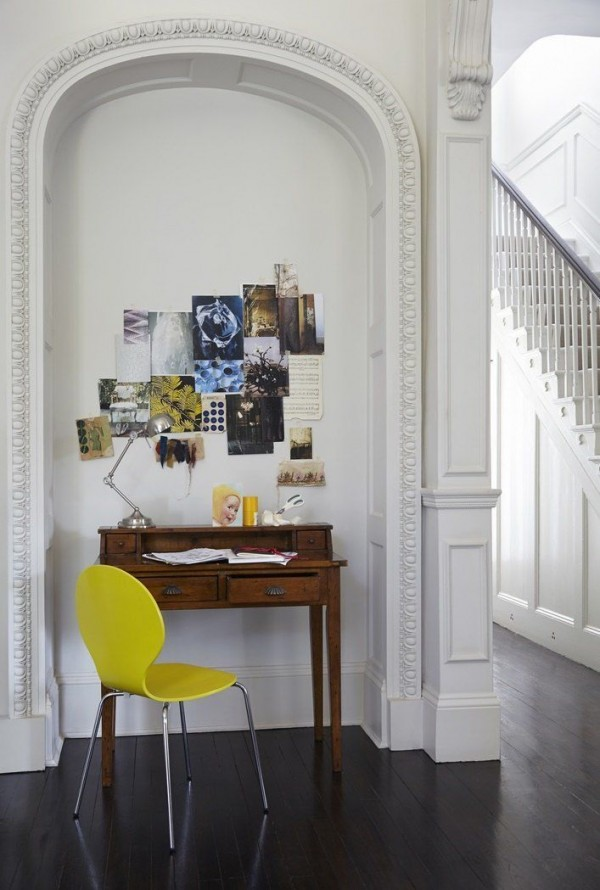 Interior design with Victorian architectural details and modern yellow furniture.