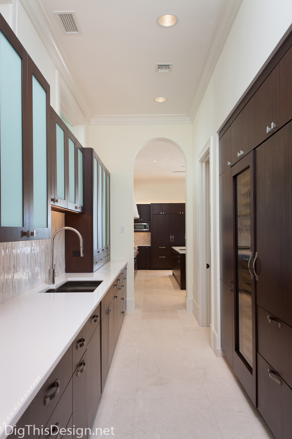 contemporary barbados style kitchen butler's pantry with dark cabinetry and white counter tops