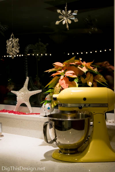 Christmas window sill decor with starfish, yellow Kitchenaid, poinsettia, silver star ornaments