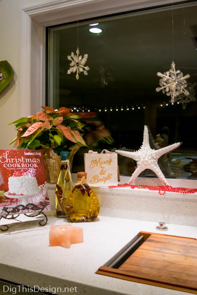 Christmas window sill decor at sink with cookbook starfish and poinsettia