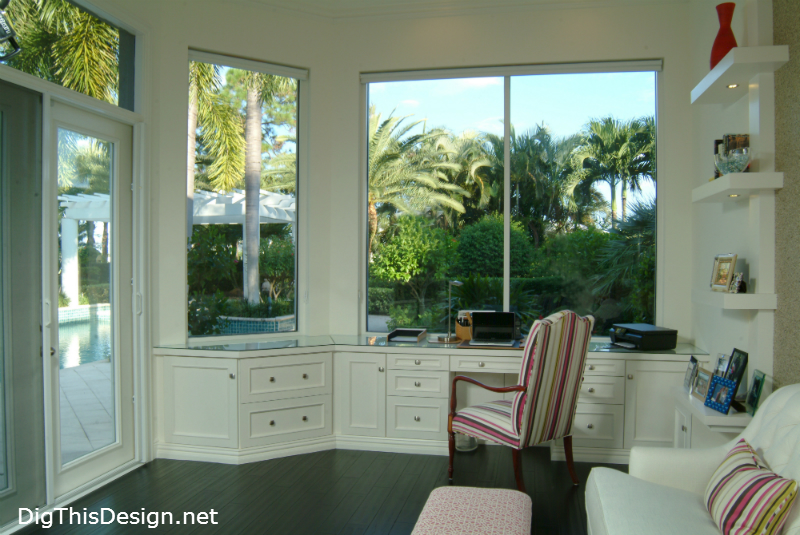 high end home office in coastal style with large window views and white interior