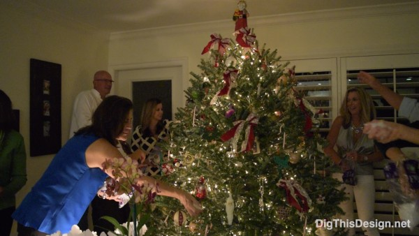 family and friends decorating a Christmas tree together