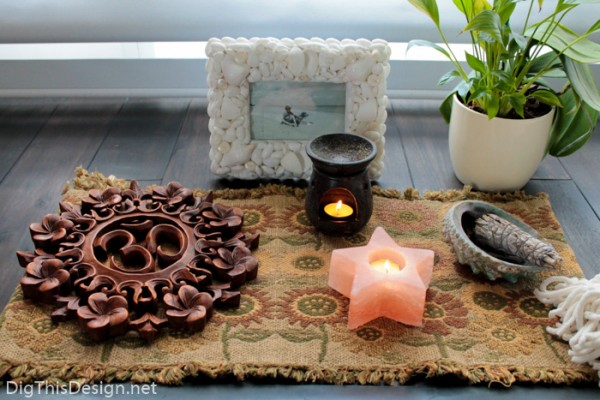 ohm, candles, essential oil, plant, and burning sage, items for a meditation space