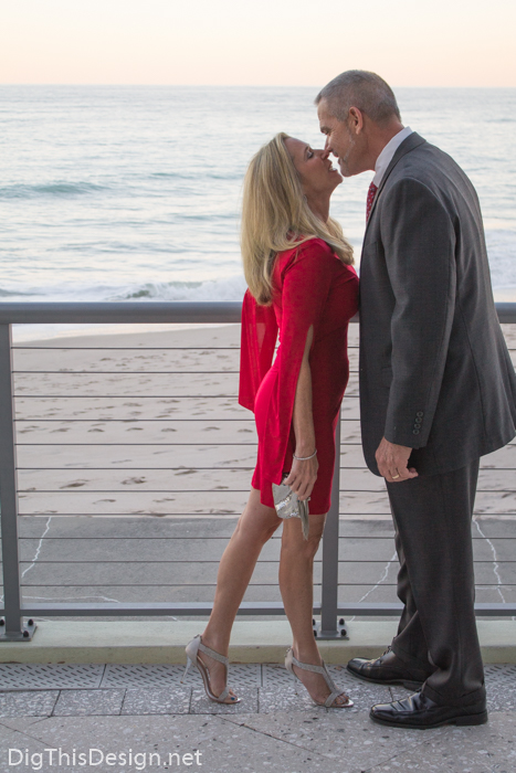 Couple on Valentine's Day, wearing red dress from Sabre Mochachino and silver accessories on the beach