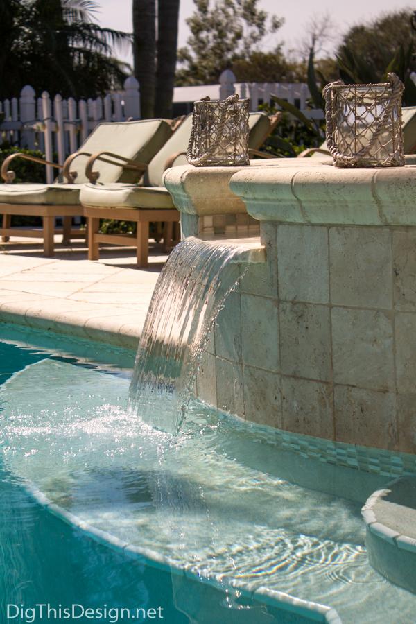 Backyard patio kidney pool with hot tub water fountain.