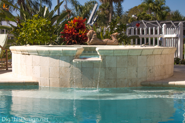 Hot tub water fountain with kidney shaped pool.