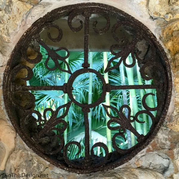 Old wrought iron medallion inbedded into the coral wall of the Spanish kitchen at McKee Botanical Garden.