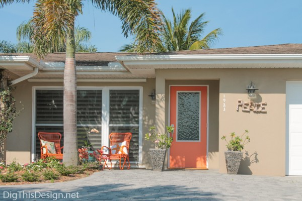 View of the house with completed front porch project accented with orange.