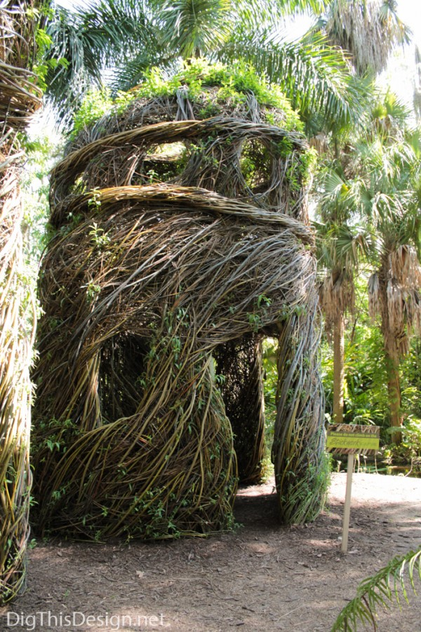 Stickwork garden hut sculpture with windows and doorways made from live saplings and tree branches by artist Patrick Dougherty.