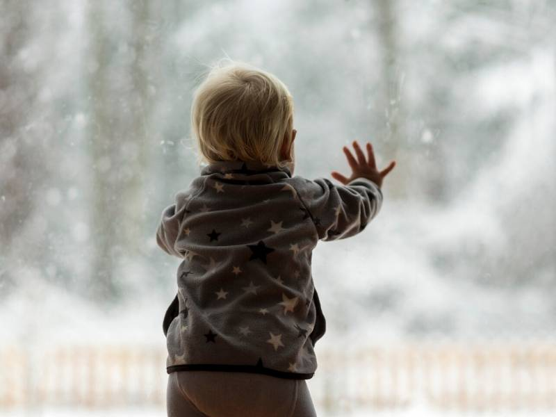 Baby Looking out Window at Snow
