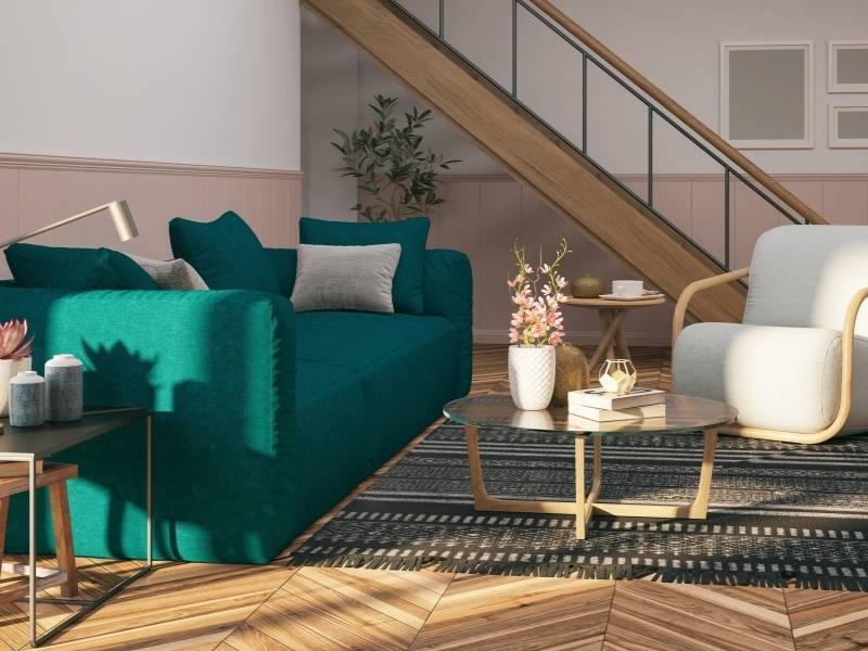 How To Add Color to Your Living Room - dark teal sofa with native pattern rug in modern room.