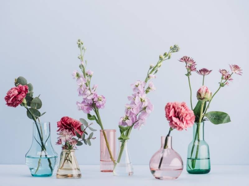 Flowers in glass vases of blue, pink and green