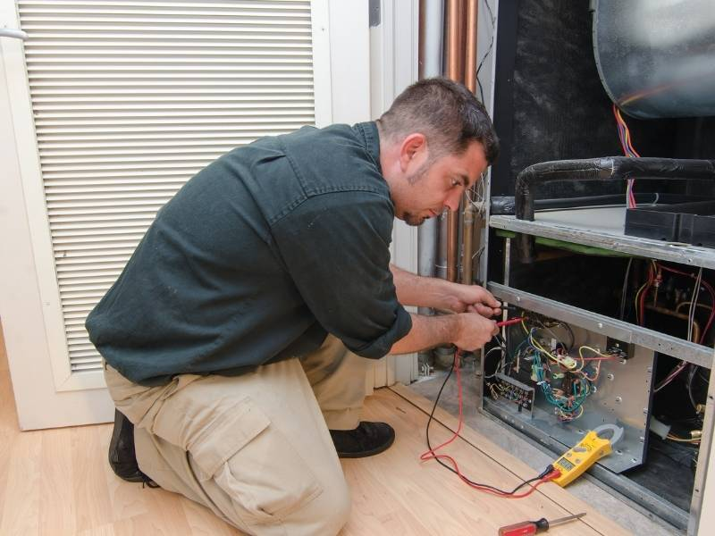 A Guide to Identifying When Your AC Might Need Repairs - HVAC Repairman testing circuits.