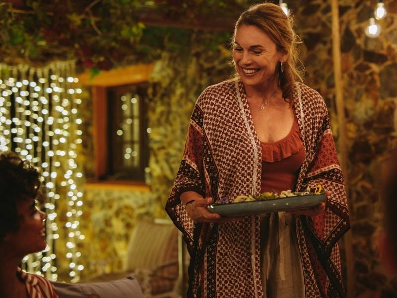 Hosting an Outdoor Evening Dinner Party - woman serving guests at an outdoor party.