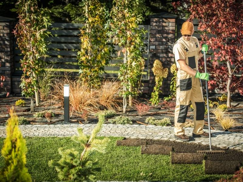 5 Benefits of Hiring a Landscaping Service for Your Yard - man working in yard rolling out new grass.