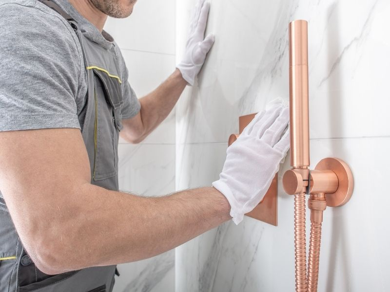 The 13 Essential Signs that Your Bathroom Needs a Remodel - photo of a plumber fitting copper fixtures to a marble shower wall.