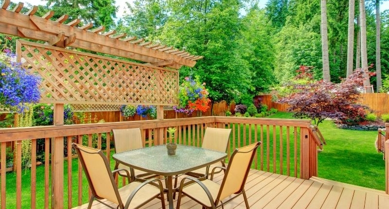 How To Create A Summer-Ready Patio - Patio deck surrounded by a lush green grass lawn.
