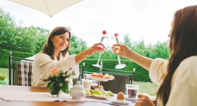 How To Create A Summer-Ready Patio - Friends toasting over a champagne breakfast on the patio.