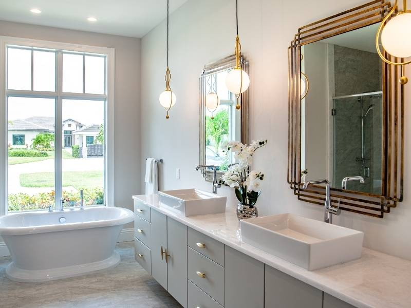 Modern bathroom with 3 pendants hanging over long his and her sinks.