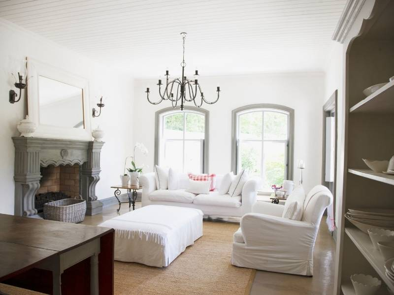 Inspiration for Chandeliers - Large rustic chandelier over classic living room white on white with grey trim.
