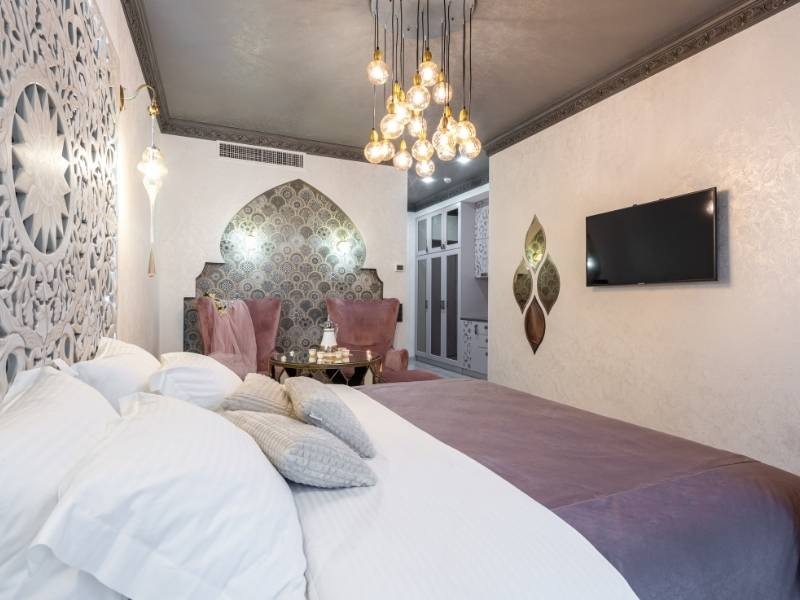 Modern multiple round glass balls hanging over persian style bedroom. Very luxurious!