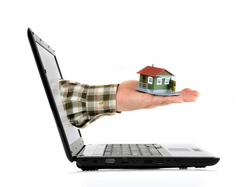 Looking Online to Buy Properties Consider These 5 Tactics! Laptop with mans hand holding a model home reaching out from the screen.