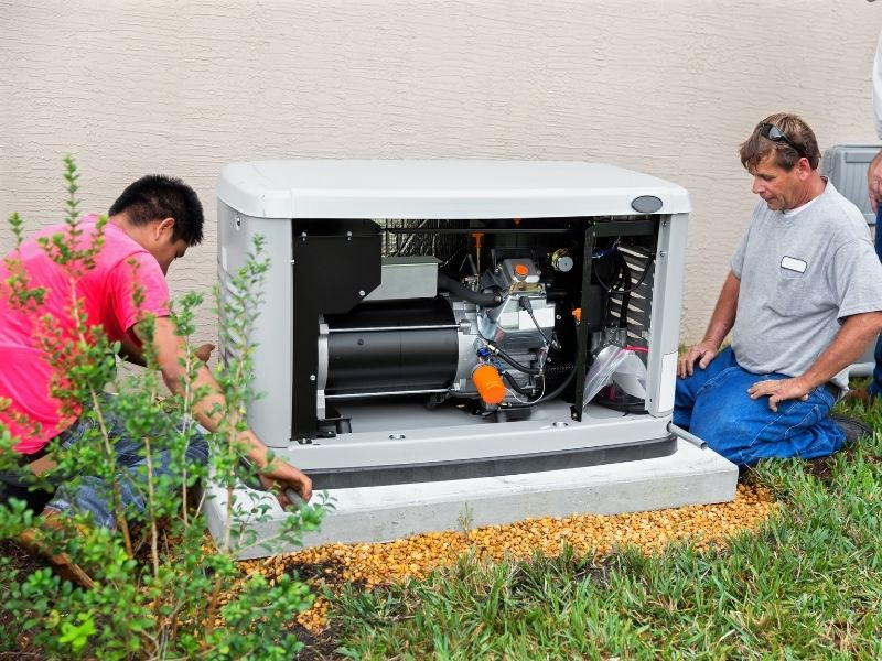 Electricians installing a whole house emergency generator for hurricane season.