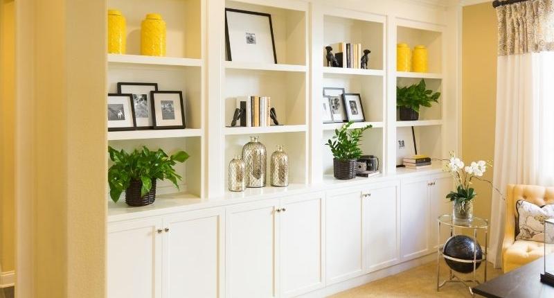 White custom shelving for a yellow wall.